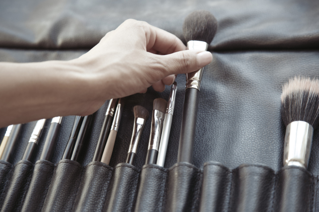 Hand of makeup artist selecting cosmetic brush from kit