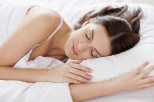 Woman sleeping. Beautiful young woman sleeping while lying in bed