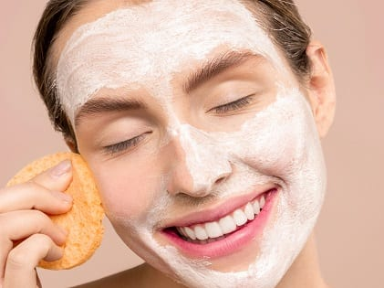 woman-smiling-while-cleaning-her-face